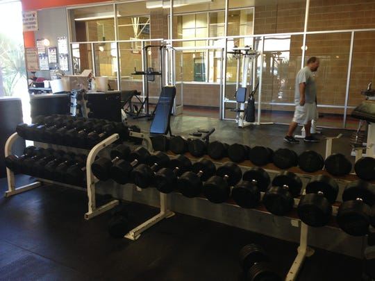 The weight racks are loaded with equipment for gym users.