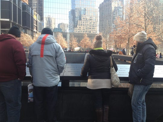 Visitors reflect at the 9/11 Memorial during a tour