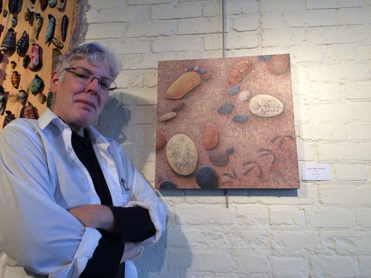 """Valerie Berkely poses next to her artwork """"Plover's Plight Footsteps"""" at the Center for the Visual Arts in Wausau on Sept. 12."""