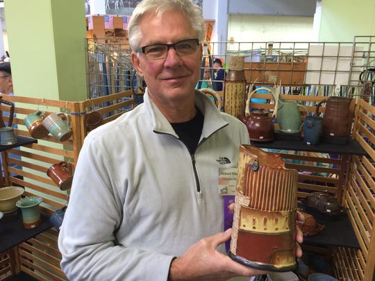 Richard Milheiser holds one of his favorite creations, a vase, at Art in the Park on Sept. 12 at Wausau's Marathon Park.