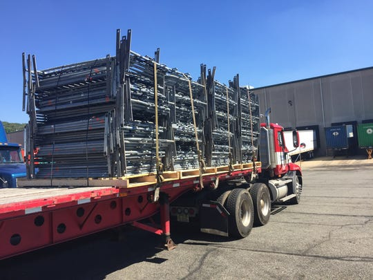 A truck is loaded with steel barriers at specialty