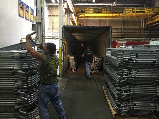 Workers load a truck with steel barriers at specialty