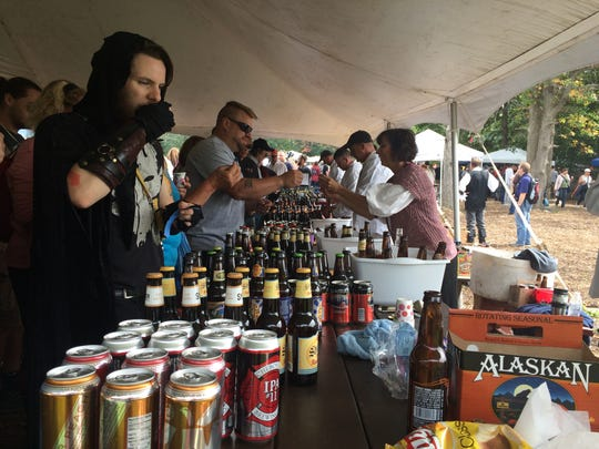 Dane Carten, 23, of Roseville tastes one of the many local and national beers available for sampling Sunday, Sept. 20, at the 37th annual Michigan Renaissance Festival in Holly.
