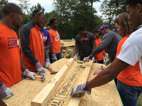 Clemson players lend a helping hand at Habitat for Humanity site Tuesday afternoon.