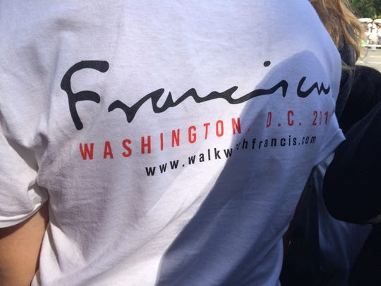 A parade-goer sports a #WalkWithFrancis campaign T-Shirt.