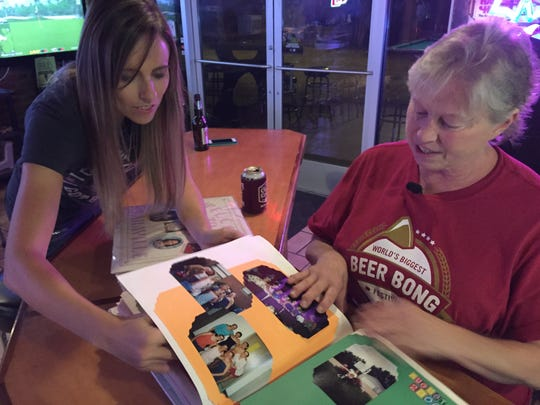 Sara Erlandson looks through scrapbooks with her mother, Kathy Gutting.  Sara danced competitively through her teens.