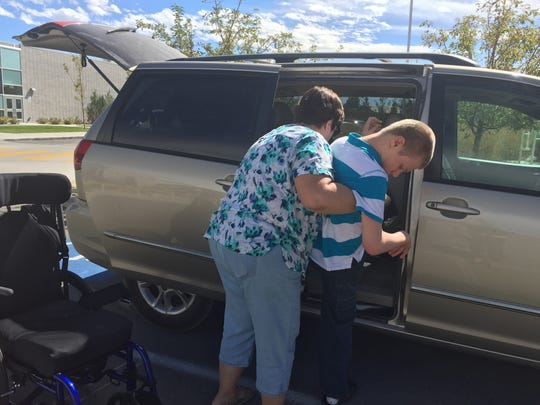 Pam Berek helps her son Carson in to her car on Thursday at Depoali MIddle School.