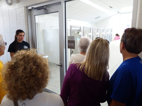 Brie Rios, left, a part-time kennel assistant at the new Iowa City Animal Care and Adoption Center, gives a tour of the facility during an open house on Saturday, Sept. 26, 2015.