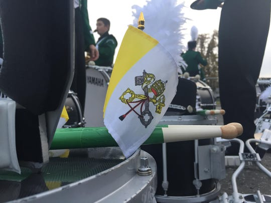 The flag of the Vatican City decorates instruments of the Bishop Shanahan High School Marching Band.