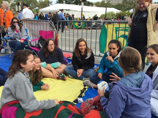 A group of UNC-Wilmington students, who a members Catholic Campus Ministry, play the game Catchphrase to pass time before Pope Francis leads 4 p.m. Mass on Sunday.