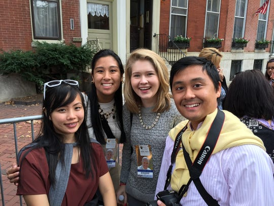 Mike Dejos and his wife Nhu Dao pose with friends as they await celebration of Mass with Pope Francis Sunday.