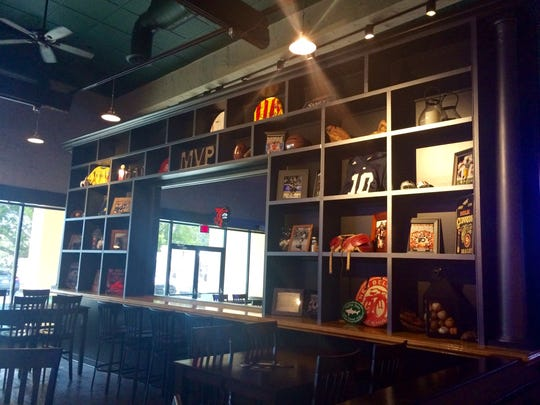 A wall of sports memorabilia divides the bar from the