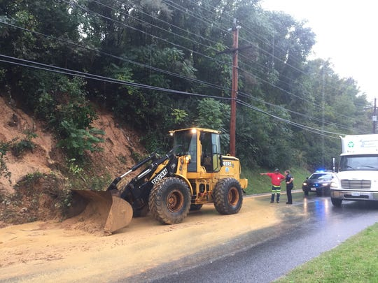 Traffic slows as a Staunton utility worker tries to clear mud and debris from U.S. 250.
