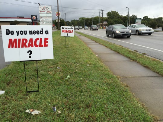 Signs up in front of Victory Christian Center, 1641 Middle Tennessee Blvd. in Murfreesboro, encourage passers-by to stop if they 'need a miracle.' If they stop, Scott Coy will pray for them.