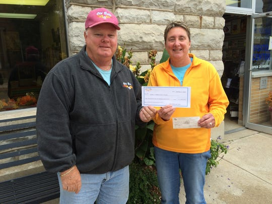 Russ Gilman of the Old Bolts Car Club hands Nancy Hutchinson of Adopt a Soldier a $1,400 check.