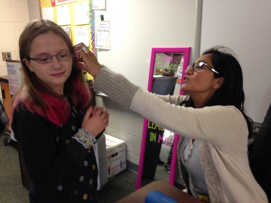 Phoebe Fettes, a fifth-grader at Algonquin Elementary School is fitted for a new pair of eyeglasses Thursday morning at the school. Pearl Beach Lions Club led the project providing glasses and eye exams to students there.