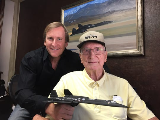 Former test pilot Bob Gilliland, seated, and son Robert Gilliland at Robert's office in Palm Desert on Sept. 25, 2015. In the background is a painting by aviaton artist Stan Stokes of Bob's first flight aboard the SR-71 Blackbird on Dec. 22, 1964.