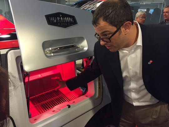 Russell Weiner, president of Domino's USA, demonstrates how a driver might use a warming drawer in the company's newly outfitted delivery car known as a DXP. Oct. 21, 2015.