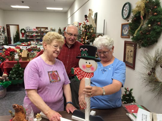 Shirley Wussow, holiday store coordinator (left), Chuck Weiss, and Janet Anderson, assemble a snowman card holder at the Bethesda Christmas Shop on Wednesday, Oct. 21, 2015.