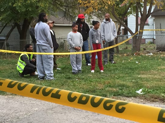 Nearby residents gather across the street from the Near Eastside Indianapolis residence in the 3400 block of East 9th Street, Indianapolis' latest homicide, which occurred early Thursday morning, October 22, 2015.