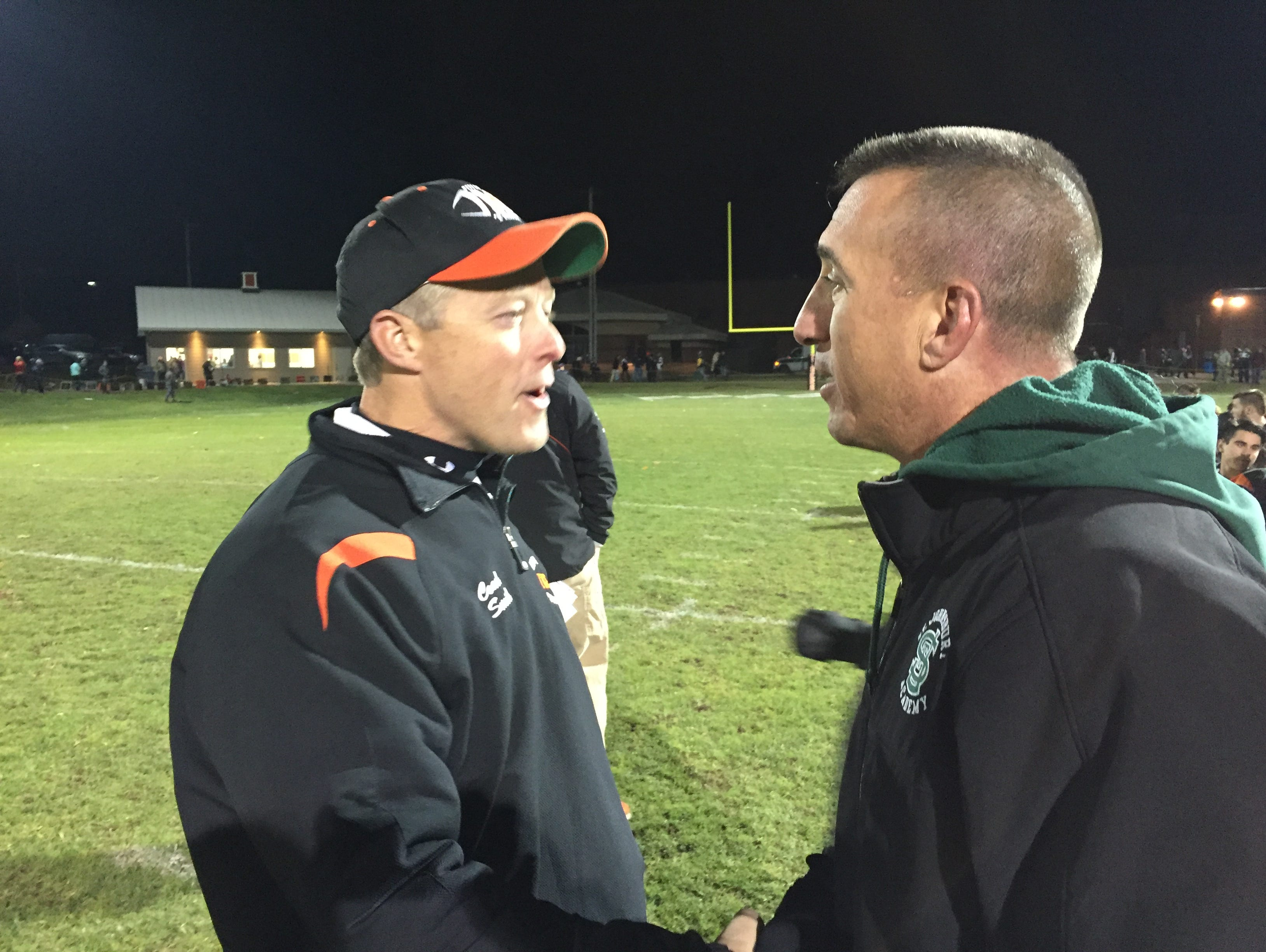 Middlebury coach Dennis Smith, left, and St. Johnsbury coach Rich Alercio, shake hands following the Tigers' 38-12 win Friday night in Middlebury.