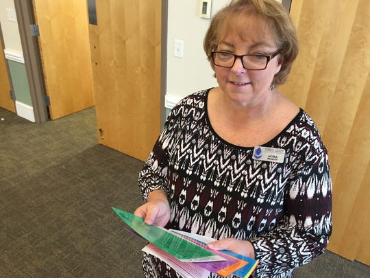 Myra Beasley with the Domestic Violence and Sexual Assault Program holds cards that direct participants on what characters to portray in a domestic violence simulation Friday.