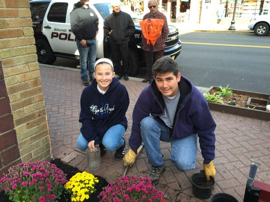 Hannah Kriney, great-great granddaugher, and Ken Kriney, great grandson, plant flowers at the Samuel Kriney Memorial Park in Bround Brook for Make a Difference Day.