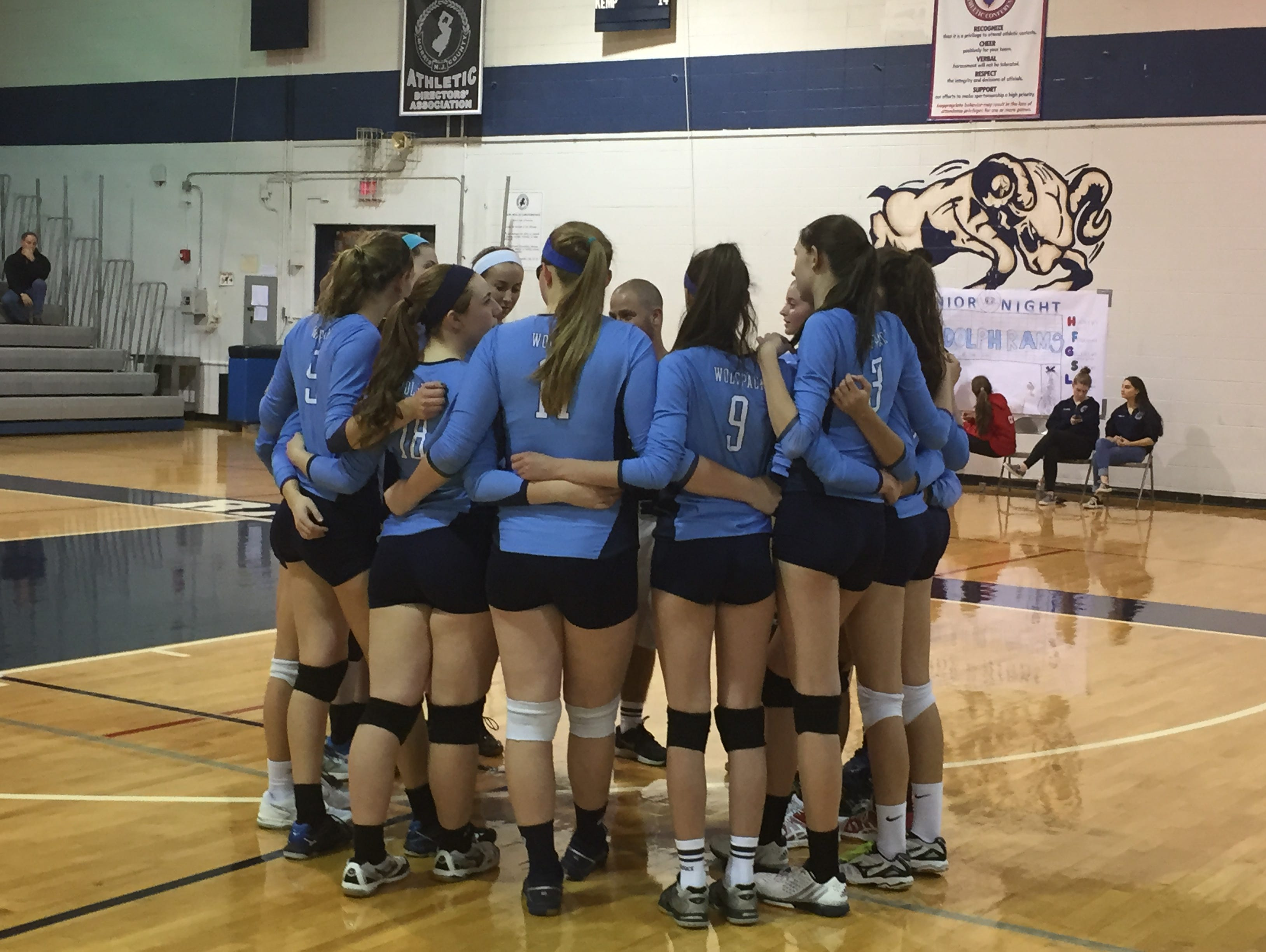 The West Morris volleyball team gathers before the third game of the Morris County Tournament semifinal on Saturday night.
