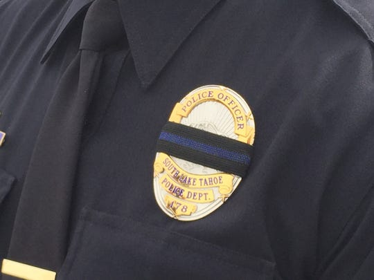 South Lake Tahoe Police officers wore a black band with a blue strip over their badge in remembrance of Officer Mark Hounsell and his wife Jeanne who died Oct. 17 in a rollover accident.