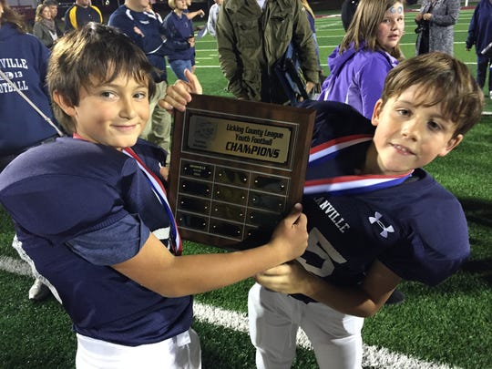 Two Granville Navy players show off the championship plaque Sunday after their team's 29-6 victory against Heath Brown in the Licking County League Youth Football Varner Division final.