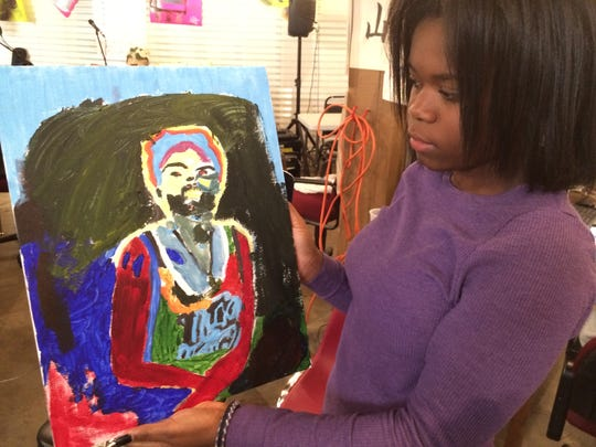 A 16-year-old local artist shows off a self-portrait she painted during a recent workshop at ArtForceIowa.