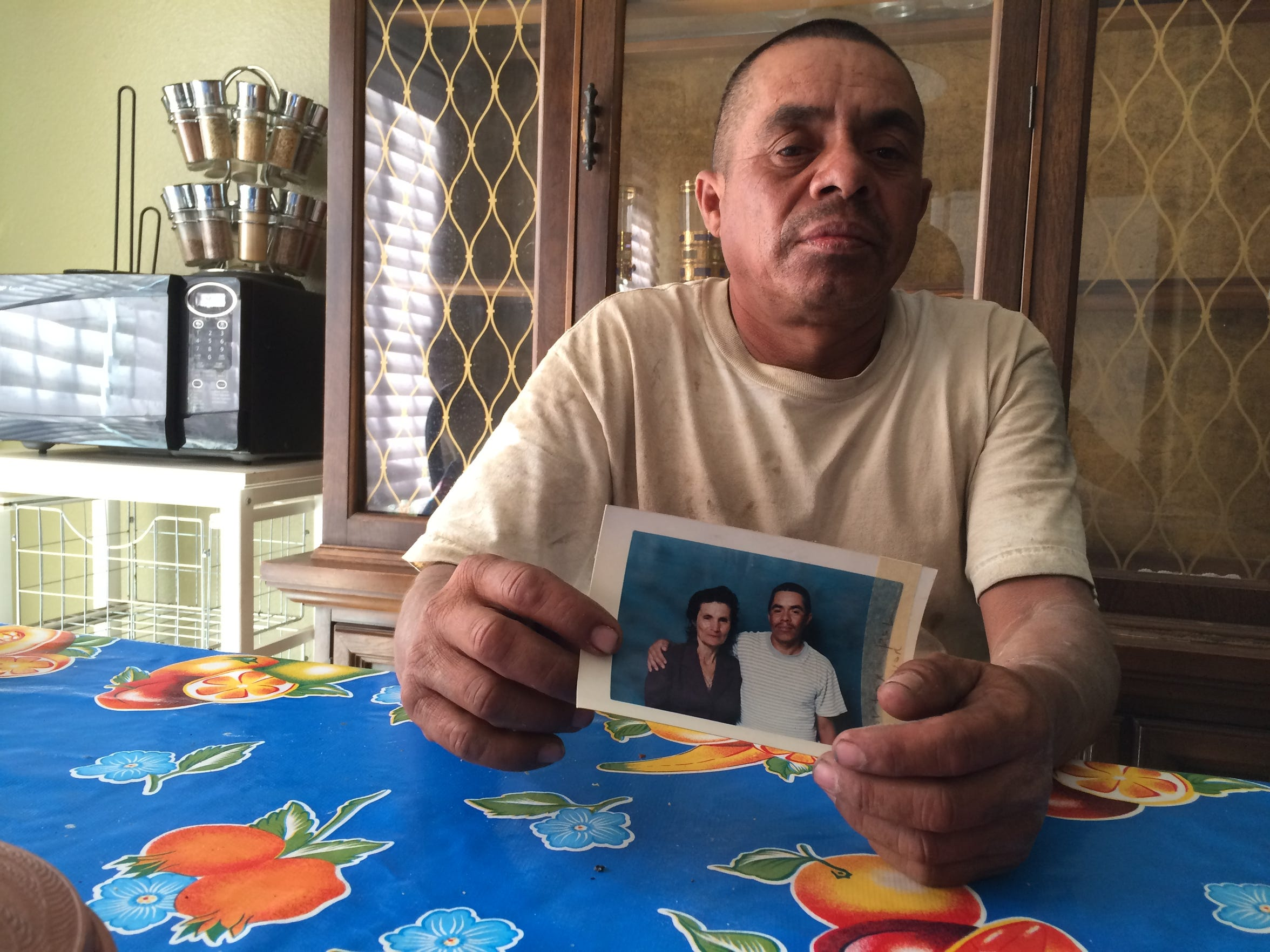 Francisco Alvarez Bautista holds a photo of him and his late mother, Maria de Jesus Bautista. Maria died from complication due to heat exposure while working in the grape fields in Thermal in 2008. Family members said the contractor failed to comply with the state's Heat Illness Prevention Regulation.