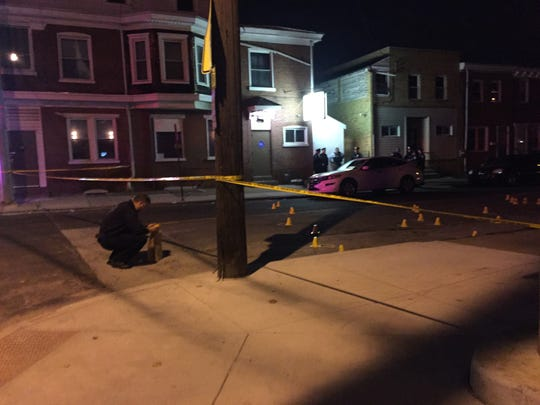 A Wilmington police officer investigates a shooting scene in the Southbridge neighborhood on Monday.