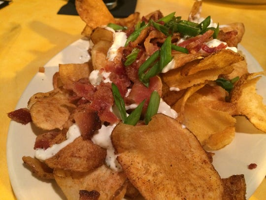 House made barbecue-flavored chips with blue cheese dressing (also house-made), maple bacon and green onions is an appetizer from The Standard.