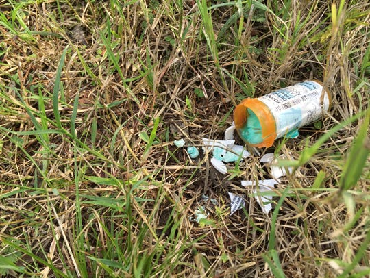 An open pill bottle outside of a vacant house in the
