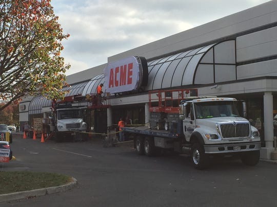 Workers erect an Acme sign on the former A&P supermarket