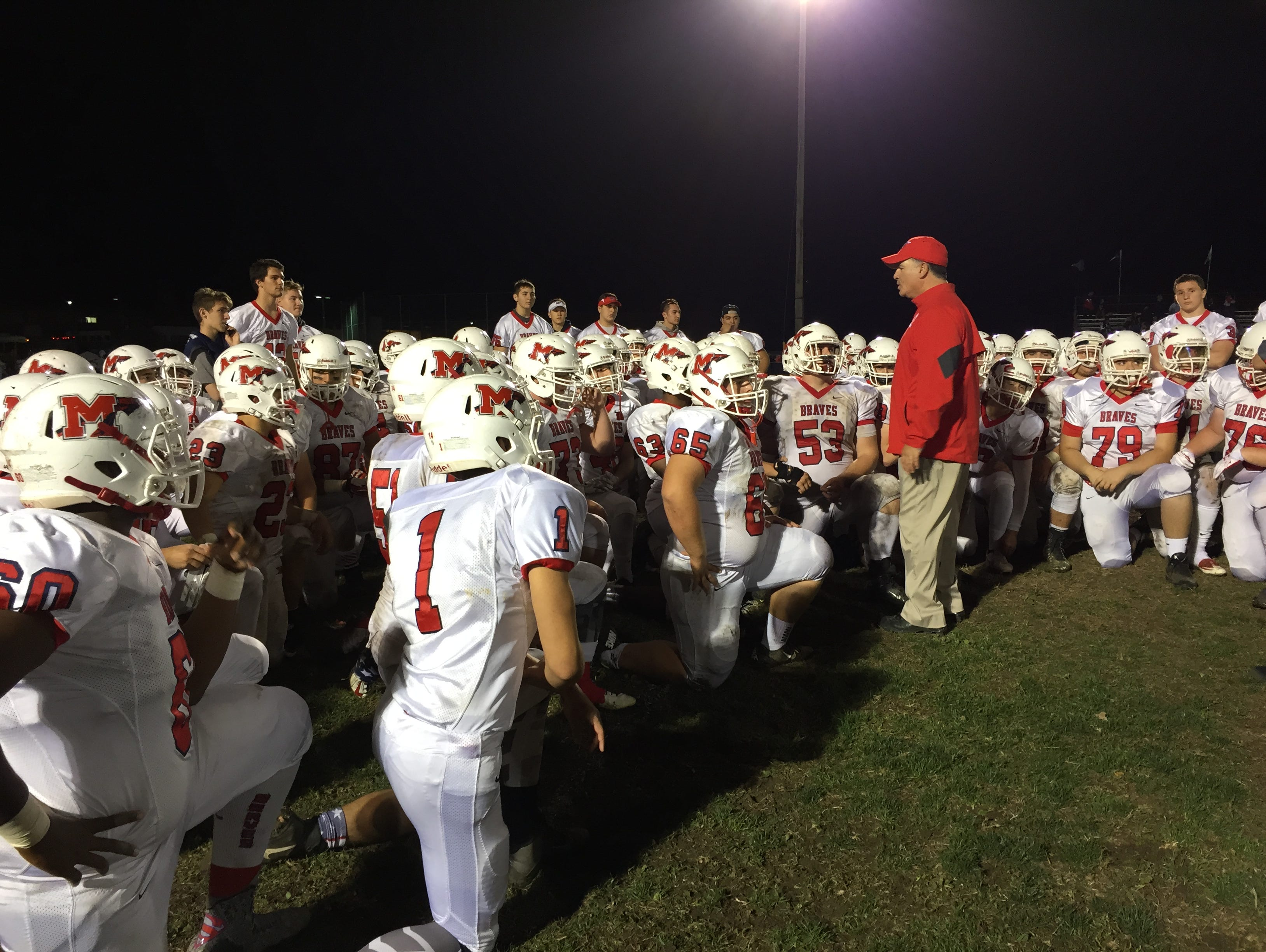 Manalapan football coach Ed Gurrieri congratulates his players after their 42-0 win over Howell.