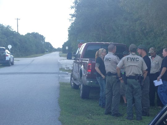FWC officers huddle Saturday afternoon in the area of residence the snake escaped on Friday.