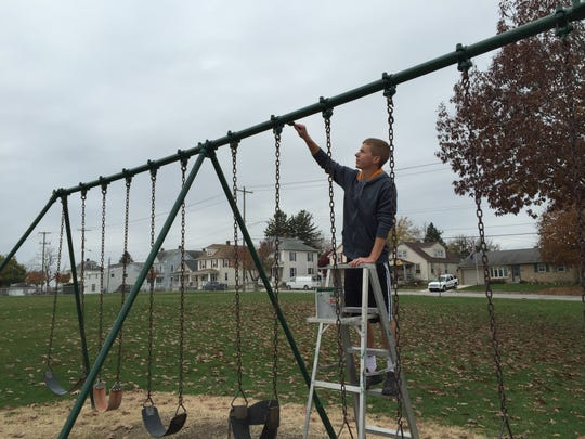 Hanover High School Senior Ben Hutton gives the swings a fresh coat of green paint. Hutton is working on the Moul Field playground as part of a school project.