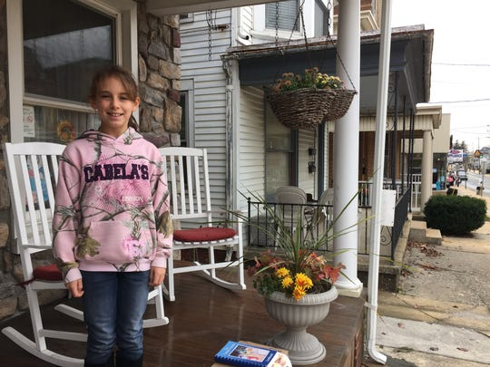 Abigail Heffelfinger, 11, stands outside of her grandmother's home on Saturday, during the 7th annual Christmas in Dallastown event. Her brother, Jason, 9, has a progressive disorder called mitochondrial DNA depletion syndrome. Their family is selling custom cookbooks to help cover medical expenses that insurance does not pick up.