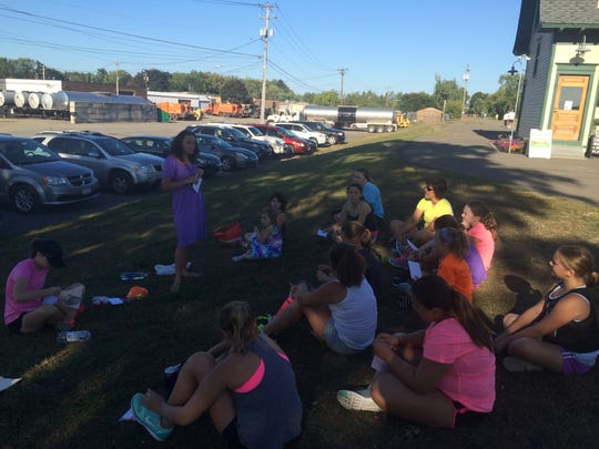 Rachel Johnson, standing, a teacher at Johnson City High School who has two young children and qualified for the Boston Marathon, spoke to the girls in the GROW program about  setting goals and also about balancing running with a busy schedule.