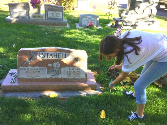 Fifth grader Daytona Horspool cleans the area around her grandpa's grave who served in the Vietnam War.