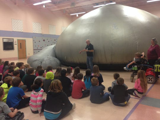 Algonac Community Schools fourth graders listen to David Killion, a presenter with mobile ed productions, inc., before climbing into the company's travelling sky dome planetarium, set up in the gymnasium of Millside Elementary.