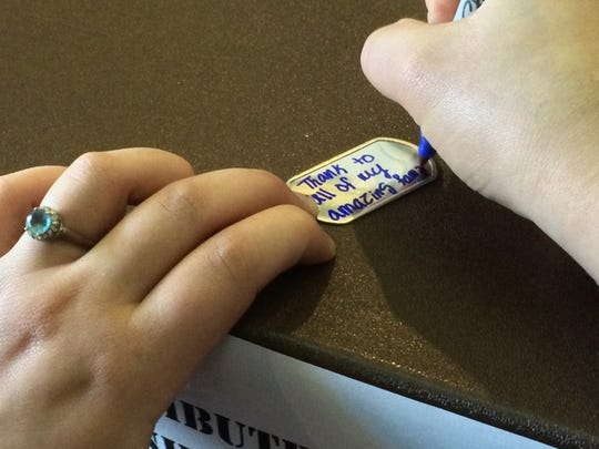 A student at UWO writes a thank-you note on a dog tag