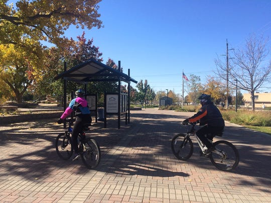 Candy Pulte and her husband, Matt Pulte, ride their bikes on Sunday at Berg Park in Farmington.