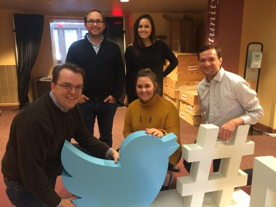 Adam Sharp, left, of Washington, D.C., and a few of his Twitter coworkers set up the #DemDebate sculpture at Drake University's Sheslow Auditorium.