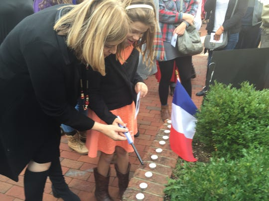 Mayor Megan Barry joins a young girl named Tennessee to light a candle after a gathering  to honor Paris on Nov. 15, 2015.