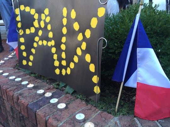 "A makeshift memorial for Paris outside of the Little Gourmand market in Green Hills. The sign says ""peace"" in French."