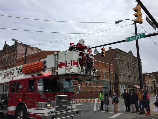 Santa Claus rides a fire truck up Main Street Hill in the Holiday Parade Saturday