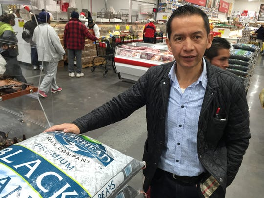 Osvaldo Carrera, manager and co-owner of Food Fair supermarket in Spring Valley, alongside a 100-lb bag of black beans (selling for $73.99) in  the newly opened store on Route 59 in Spring Valley. Carrera said Food Fair, a hybrid traditional market and bulk warehouse, draws customers from New City, Nyack, Suffern and beyond, representing cultures from Central and South America, Russia and Poland.